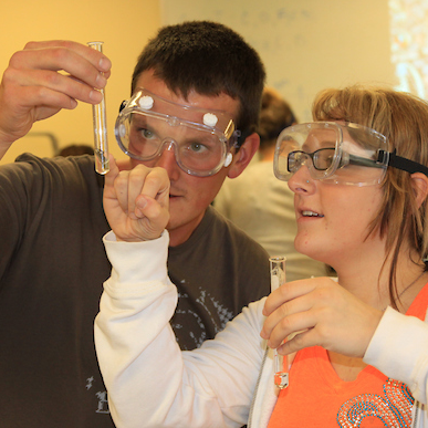 Chemistry students examining chemical in a test tube.